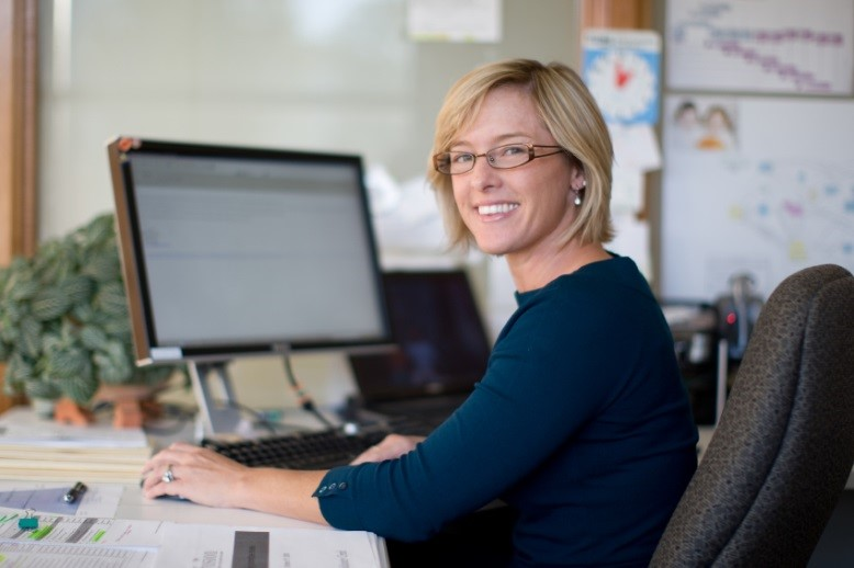 Woman sitting at desk turned away from computer screen to smile at camera
